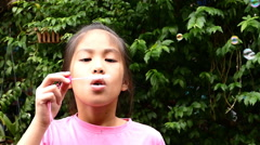 Happy child blowing soap bubbles in spring park. Slow motion Stock Footage