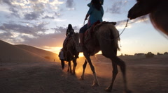 Tourists ride camels walking on desert at sunset Stock Footage