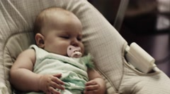 Adorable little baby sway on swing in apartment. Baby dummy. Hands movements Stock Footage