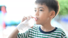 Little boy drinks water from a bottle after excercise Stock Footage