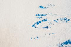 Plaster white painted wall with blue spots Stock Photos