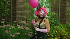 Clown woman look at garden balloon Stock Footage
