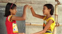 Two girl students play a fun clapping game in front of a chalk board Stock Footage