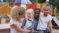 4K Portrait smiling mixed family at outdoor adventure playground Stock Footage