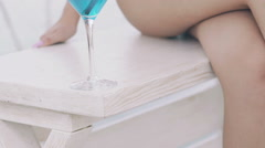 Close up goblet of blue cocktail near bare woman's legs and hand. Slowly Stock Footage