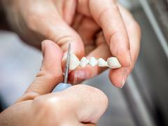 Dental technician molding teeth Stock Photos