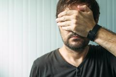Casual adult male covering face and eyes with hand Stock Photos