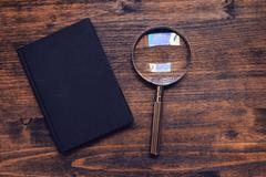 Loupe magnifying glass and notebook on wooden desk, top view Stock Photos