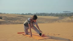 Young slim woman doing stretching exercises on sand beach. Fitness female Stock Footage