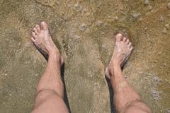 Legs men on the sea sand near sea wave Stock Photos