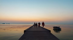 People walk on a pier in the sea sunset background Stock Footage