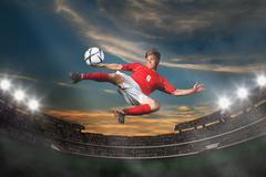 Soccer Player Kicking The Ball In Mid-Air Stock Photos