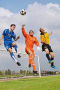 Football players aiming for the ball - stock photo