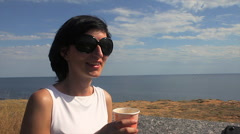Woman Taking a Sip of Coffee by Sea in the background lighthouse Stock Footage