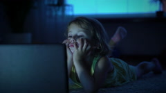 A little girl watches cartoons in the computer late in the evening. Stock Footage