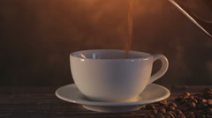 Steaming coffee on dark brown background Stock Footage