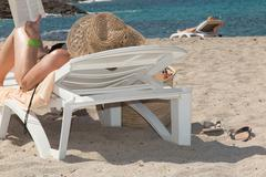 Young woman with hat relaxing on a deck chair Stock Photos