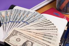 Notepad with dollar banknotes Stock Photos