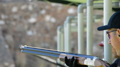Shooter aiming and firing a rifle in skeet championship Stock Footage