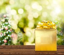 Golden present on brown wood table with christmas tree blurred bokeh light, M Stock Photos