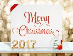 Merry Christmas red glitter text on white paper card with 2017 new year numbe - stock photo