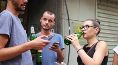 Young people drink alcohol beer and type smart phones social media public place - stock footage