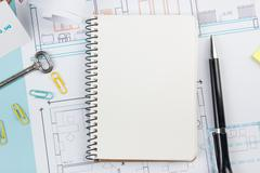 Real estate concept. Blank white notebook on architectural desk table blueprint Stock Photos