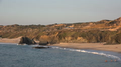 Portugal looking over coastal landscape with kids playing in the waves. Stock Footage