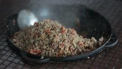 Pilaf cauldron stirred in a restaurant kitchen. Stock Footage