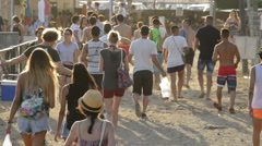 Young people walking to the entrance of concert or summer festival at sunset Stock Footage