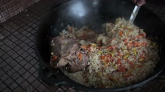 Rice with vegetables and lamb stirred kettle. Stock Footage