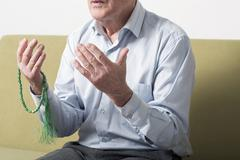 Praying hands of an old man holding rosary beads Stock Photos
