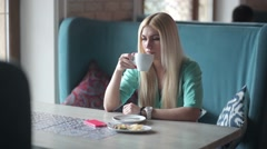 Blonde drinking coffee and looking at her watch. Stock Footage
