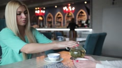 The blonde pours a cup of tea from a teapot. - stock footage