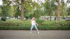 young beautiful girl dancing in a park. woman in jeans dancing in the street - stock footage