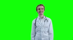 Positive doctor looking into camera, pointing on item. Green screen Stock Footage