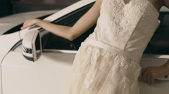 Beautiful model in a wedding dress posing for the photographer close to the Stock Footage
