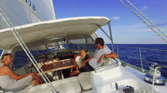 Couple on a sailboat cruising the blue ocean on a sunny summer day Stock Footage