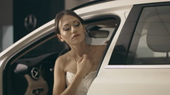 Brunette in wedding dress posing for a photo shoot sitting in an expensive car Stock Footage