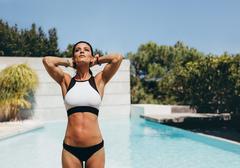 Beautiful young woman posing in a bikini next to a pool Stock Photos