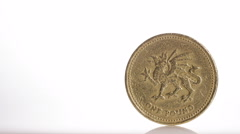 4K One pound coin balancing on white surface, with space for text - stock footage