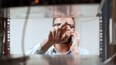 Engineer working in data room, speaking on phone. Slow motion Stock Footage