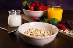 Flavoring oatmeal with white yoghurt and some berries Stock Photos