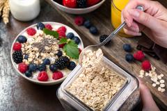 Spoon of oatmeal. Bowl with berries. - stock photo