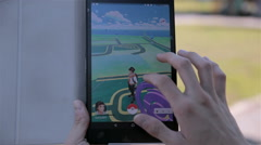 Pokemon Go app being played by a man on his tablet Stock Footage