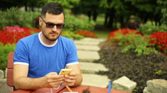 Man is sending sms on a phone in the park Stock Footage