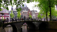 Two persons ride  bikes on pictorial bridge in Amsterdam, Holland Stock Footage