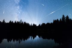 Falling stars Lake pine trees silhouette Milky Way Stock Photos