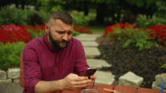 Man is typing sms in the park Stock Footage