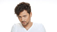 Displeased young handsome man looking at camera over white background. Slow Stock Footage
